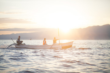 Tourists On Boat In A Sea At Sunset