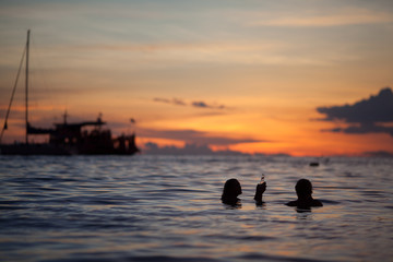 Rear view of silhouette couple having drinks in sea against cloudy sky at sunset