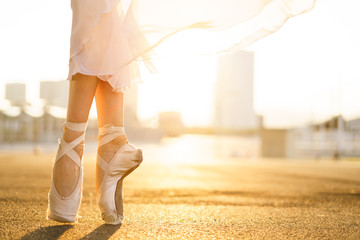 Ballet dancer in point shoes and flying skirt in sunshine