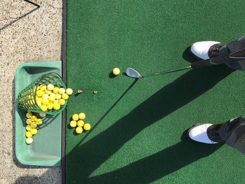 Low section of man practicing golf at driving range