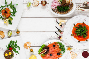 Delicious mediterranean snacks on white table, free space, flat lay. Tasty plates with various salads, smoked fish and meat on white wooden background, copy space for text