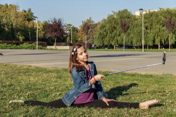 Юная девочка занимается гимнастикой, йогой на зеленой траве и фотографирует себя. Здоровый образ жизни.