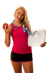Fit blonde woman holding scale gesturing healthy lifestyle and w