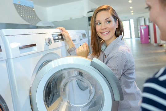 shopper choosing washing machine in household appliance store