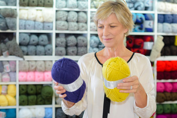 Lady in shop choosing between two balls of wall