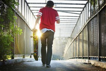 Rear view of man carrying skateboard while walking on bridge