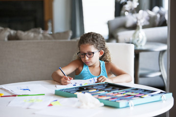 Girl coloring with felt tip pen on paper at table