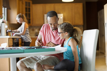 Father coloring with daughter at table