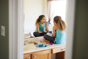 Girl applying make-up in mirror at home