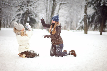 Two girls friends or sisters playing snowballs in the snow in the winter in a warm winter clothes