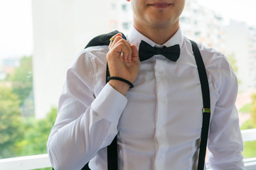 Fashion detail of groom wearing bowtie.