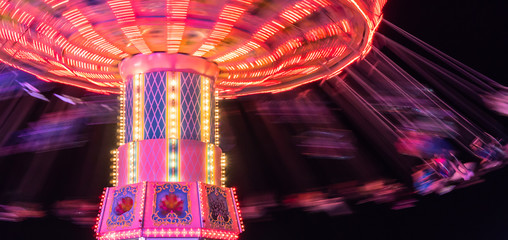 people  spinning around fast and high in swings at the brightly lit ride at the county fair