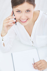 Young smiling asian businesswoman talking on the phone. Top view. Business, office, school and education concept.