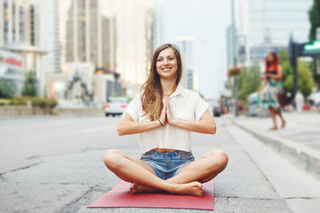 Portrait of slim fit sporty young white Caucasian hippie hipster woman with long blond hair meditating doing yoga exercisers in city street, healthy lifestyle concept.