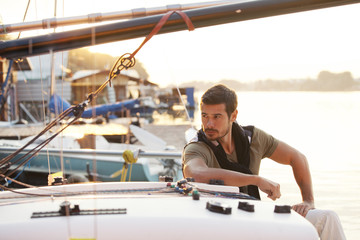 Handsome man on a sailing boat in sunset