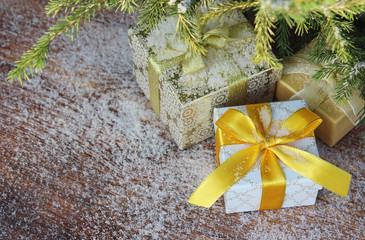 Gift boxes with bows on wooden background and fir-tree branches