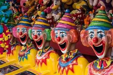 Row of clown heads in carnival side show alley with prizes