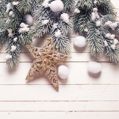 Christmas star and branches fur tree on white  wooden backgroun