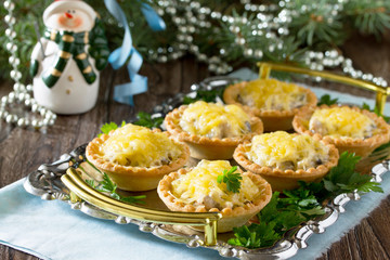 Holiday appetizer: tartlets with mushrooms and meat on a celebra