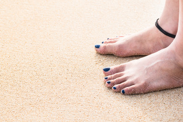 woman feet with knit leather anklet,  matt dark blue nails color, standing on sand at beach, selective focus