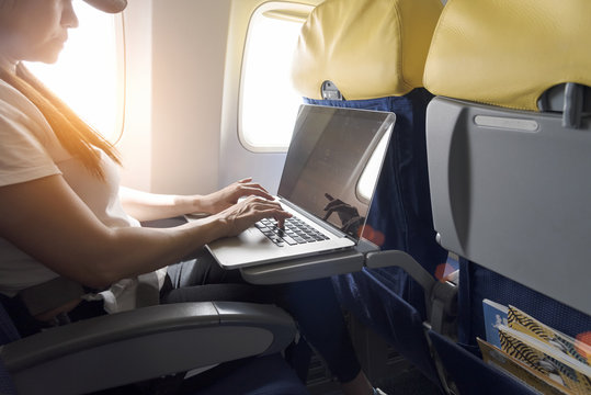 asian tourist  woman using  laptop at airplane with sunlight
