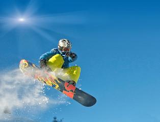 Snowboarder springt vor blauem Himmel und Sonnenschein