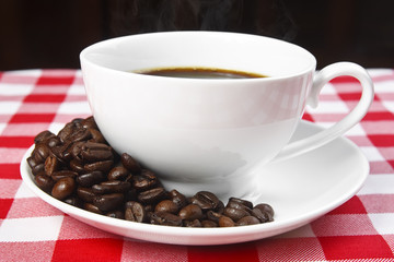 close up beans & hot coffee in white cup on table with red tablecloth and black background