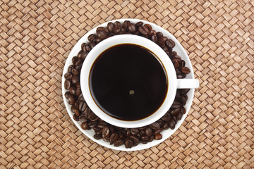dark coffee with beans in white cup on rattan table