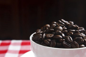dark beans coffee in white cup on table with red tablecloth and black background