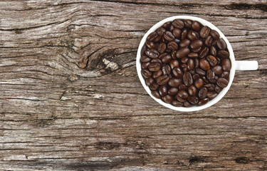 dry beans coffee in white cup on ancient wooden table