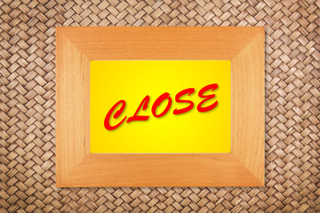 close text in modern picture frame on rattan