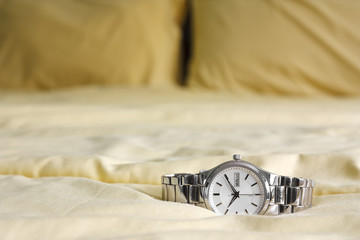 silver watch on yellow bed