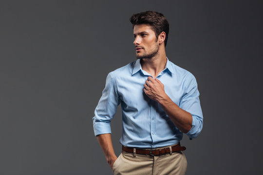 Portrait of a casualman buttoning his shirt isolated