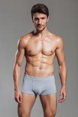 Portrait of a happy muscular man in underwear standing