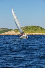 Sailboat floating on sea during regatta. Dark blue sea level, sm