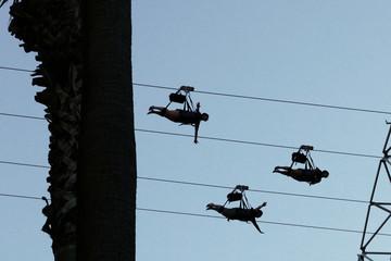 Silhouette von drei Person an einer Zipline gegen den Himmel