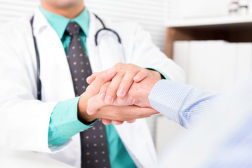 Doctor holding senior male patient hand