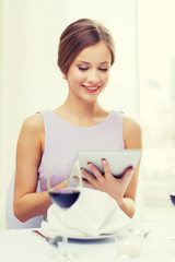 smiling woman with tablet pc computer at resturant