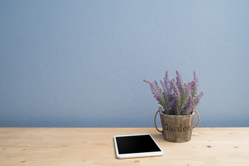 wood table with blank screen  smartphone and purple lavender flower on flowerpot.