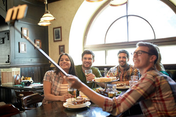 happy friends with selfie stick at bar or pub
