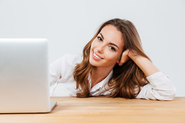 Cheerful young beautiful woman sitting at the desk with laptop