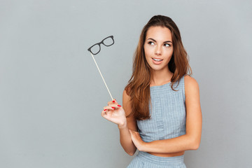 Pensive young woman with glasses props standing and thinking