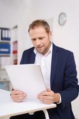 lächelnder mann im büro arbeitet mit tablet