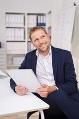 mann im büro schaut lächelnd nach oben