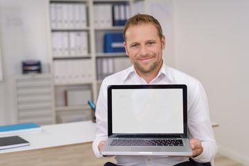 geschäftsmann zeigt stolz etwas am laptop