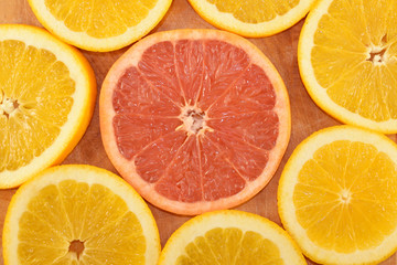 Grapefruit slice with orange slices closeup.