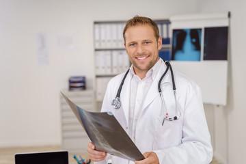 arzt steht im büro und hält ein röntgenbild in den händen