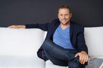 lächelnder mann sitzt entspannt auf einem weißen sofa