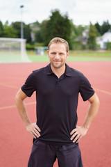 trainer steht auf dem sportplatz