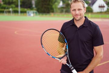 lächelnder mann mit tennisspieler auf einem sportplatz in der stadt